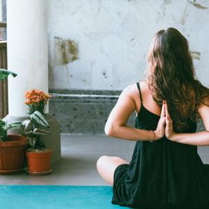 Mujer haciendo yoga en el balcón